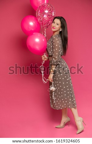 woman with perfect makeup and pink lipstick standing near air balloons with confetti and smiling. Concept celebrating, party, birthday