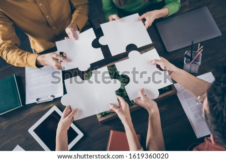 Top above high angle view photo of focused freelancer people sit table desk merge paper puzzle pieces elements trust support company career coaching concept in workstation workplace