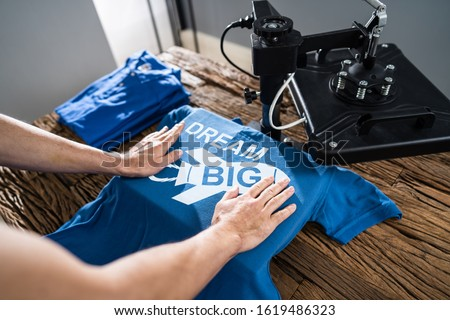 Man Printing On T Shirt In Workshop Royalty-Free Stock Photo #1619486323