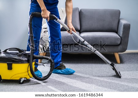 Photo Of Janitor Cleaning Carpet With Vacuum Cleaner Royalty-Free Stock Photo #1619486344