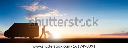 Silhouette Of Delivery Courier With Cardboard Boxes On Trolley Near The Van At Sunset Royalty-Free Stock Photo #1619490091