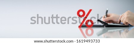Close-up Of Red Percentage Symbol In Front Of Businessperson Calculating Invoice #1619493733