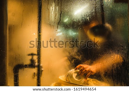 A person obstructed by kitchenware is washing bowls. View through a stained window into a Ramen restaurant at night, Asakusa, Tokyo, Japan #1619494654