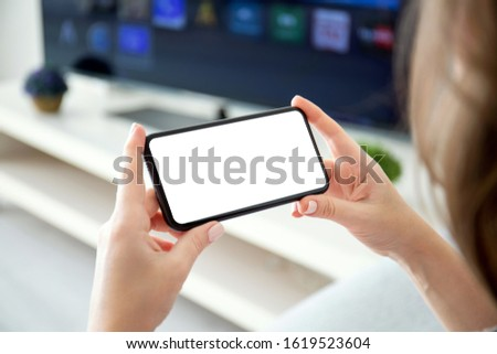 female hands holding horizontally phone with isolated screen on the background of TV in the room Royalty-Free Stock Photo #1619523604