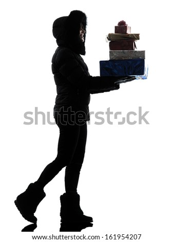 one  woman in winter coat walking carrying christmas gifts silhouette on white background