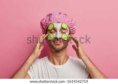 Refreshed pleased man touches cheeks, applies cucumber slices and clay mask on face, wants to have smooth clean skin, wears bathcap, takes shower, has satisfied expression, isolated on pink wall. #1619542759