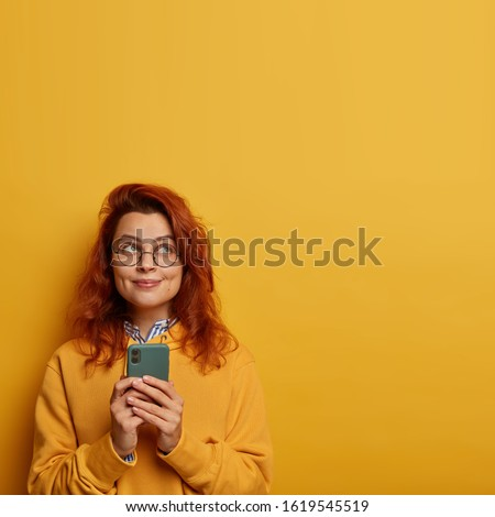 Photo of cheerful glad millennial girl with ginger hair uses mobile phone for sending text messages, thinks on message content for lover, wears yellow sweatshirt. Pleasant emotions, technology concept #1619545519