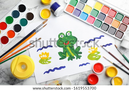 Flat lay composition with child's painting of frog on white marble table