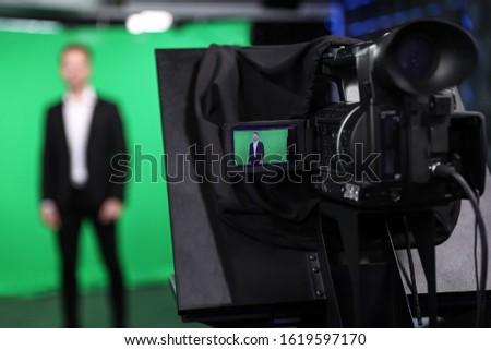 Presenter working in studio, focus on video camera screen