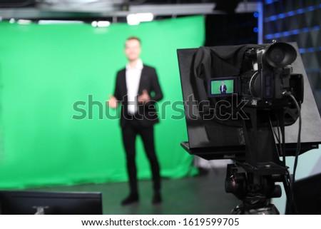 Presenter working in studio, focus on video camera