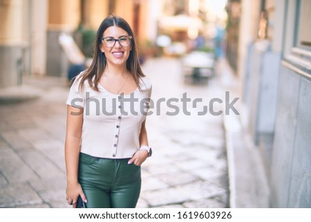 Young beautiful woman smiling happy and confident. Standing with smile on face at the town street #1619603926