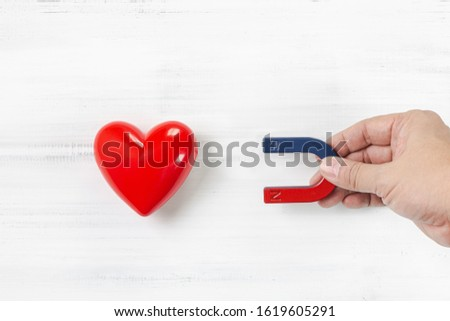 Hand of Man hold Magnet attracting Red Heart on white wood background. Love Concept with Copy Space.