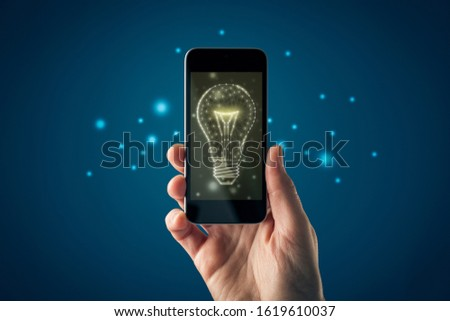 Creative company give you their creativity and ideas. Hands with smart phone and graphics light bulb - symbols of idea, creative thinking, innovations and intelligence. #1619610037