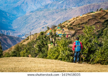 A young trekker enjoying the views of the mountains on Nag Tibba Trek situated in Dehradun Uttarakhand India. Camping on Nag Tibba trek located in Dehradun Uttarakhand India. Travel Mussoorie. - Image #1619618035
