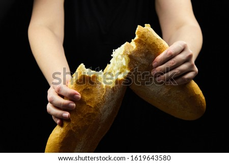 Sourdough bread, bakery product on black background. Woman holds white wheat bread. Female hands and two halves halves of loaf #1619643580