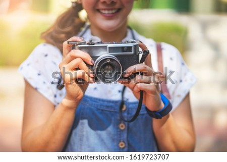 asian tourist woman holding a camera looking into the view finder and taking a pictures of the scenery, smiling joyfully and wearing a straw hat and maternity with summer sun light shining from above