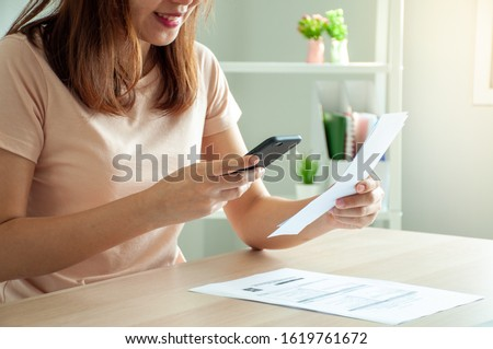 A woman uses a smartphone to scan the barcode to pay monthly phone bills after receiving an invoice sent to home. Online bill payment concept #1619761672