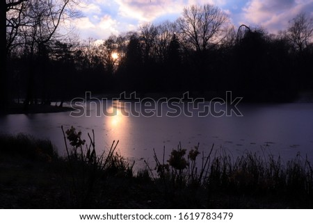 Sun reflecting off frozen lake in Lazienki Park  at sunset on a cold winter afternoon in Warsaw, Poland.  #1619783479