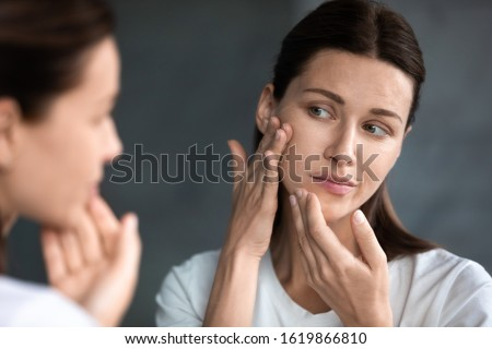 Close up unhappy sad woman looking at red acne spots on chin in mirror, upset young female dissatisfied by unhealthy skin, touching, checking dry irritated face skin, skincare and treatment concept #1619866810