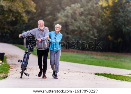 Cheerful active senior couple with bicycle walking through park together. Perfect activities for elderly people. #1619898229