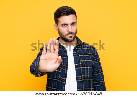 Young handsome man with beard over isolated yellow background making stop gesture