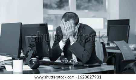 Black and white photo, business man is depressed. Headache from long work. Нe works in the office