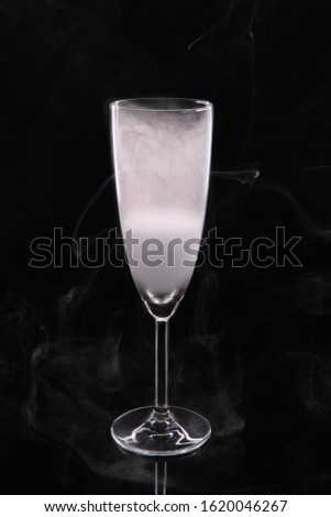 A glass glass glass for champagne filled with smoke on a black background. #1620046267
