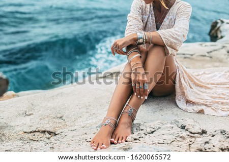 Boho styled girl wearing indian silver jewelry on the beach, tanned legs close up #1620065572