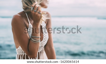 Boho styled model wearing white crochet crop top with tassels and silver jewelry on the beach #1620065614