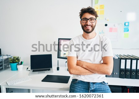 Portrait of confident graphic designer leaning on desk in office with arms crossed #1620072361