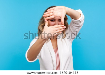 Portrait of woman in white jacket looking through photo frame made of hands, pretending to take picture with curious and positive gaze, focusing at camera. indoor studio shot isolated, blue background