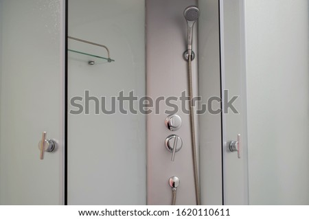 Shower cabin with chrome tap, transparent glass doors and a shelf. Apartment or hotel room. Close-up.
