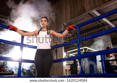 confident caucasian woman keen on boxing stand in sportive wear in ring, love boxing, box is her hobby. Professional boxer woman wearing red protective bandages on hands #1620124084
