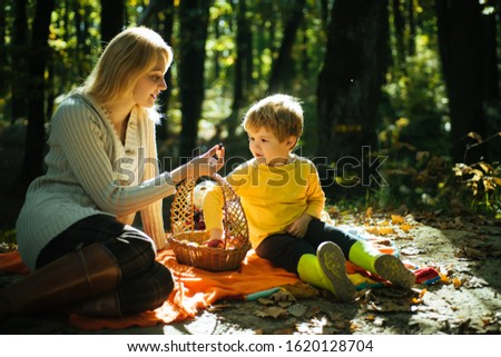 Young mother giving her little son a sweet season berrie at autumn picnic. Mum and kid sitting at picnic blanket and eating from picnic basket. Autumnal sunny warm day. Family concept