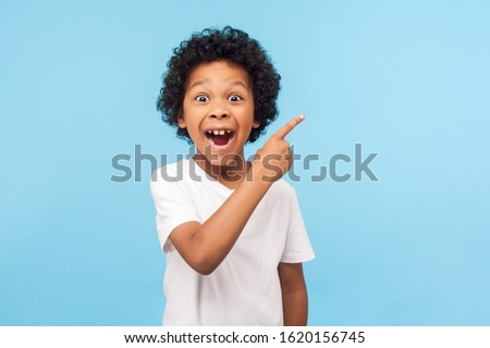 Wow look, advertise here! Portrait of amazed cute little boy with curly hair pointing to empty place on background, surprised preschooler showing copy space for promotional ad. indoor studio shot Royalty-Free Stock Photo #1620156745