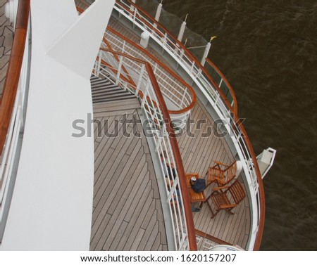 Stern of a cruise ship with a view from above of several decks with deck chairs and woolen blankets and a ship's passenger #1620157207