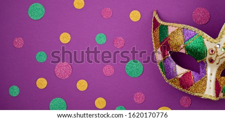Banner with Festive, colorful mardi gras or carnaval mask and accessories over purple background. Party invitation, greeting card, venetian carnaval celebration concept. Flat lay, top view, copy spa #1620170776