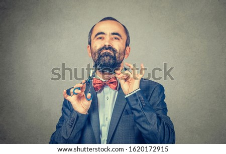 Bearded hairdresser, barber styllist  cutting styling his own beard with scissors and comb, wearing elegant jacket with red bow tie. Stylish adult man studio portrait, isolated at grey background #1620172915