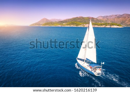 Aerial view of beautiful white sailboat in blue sea at bright sunny summer evening. Adriatic sea in Croatia. Landscape with yacht, mountains, transparent blue water, sky at sunset. Top view of boat Royalty-Free Stock Photo #1620216139