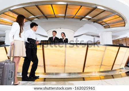 Asian Chinese woman and man arriving at front desk or reception of luxury hotel in business clothes with trolley  #162025961