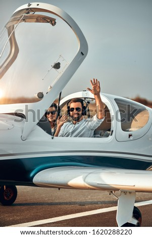 Pilot aviator welcomes waving before fly. Vertical photo