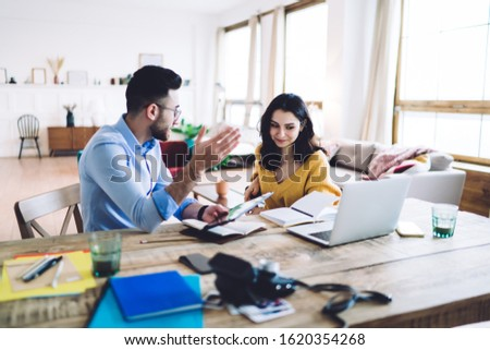 Thoughtful couple wearing casual clothes writing notes in notepads while browsing laptop and tablet and sitting at table at home #1620354268