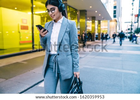 Classy executive woman in glasses wearing office clothes browsing smartphone with interest while commuting on busy city street in wireless headphones #1620359953