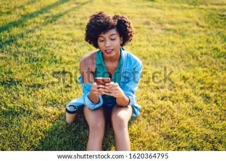 Charming pensive hipster girl millenial read posts in social networks on mobile phone sitting in park, african american female blogger browse web pages on smartphone use 4G internet connection #1620364795