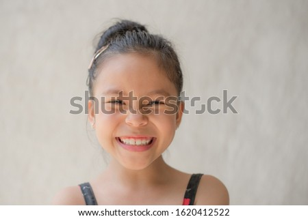portrait of a happy smiling beautiful and confident child girl, laughing child expressive facial expressions, space for text, joy on the kid face on a light background, fun and joyful concept #1620412522