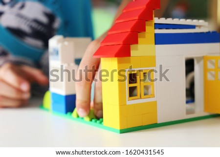 Boy builds a house with building blocks #1620431545