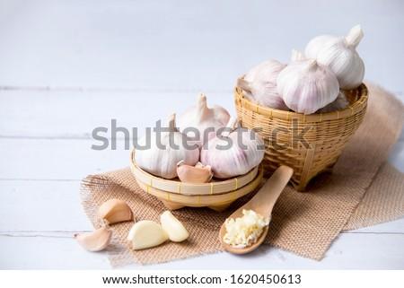 Garlic, fresh garlic,garlic clove, garlic bulb in a wooden basket. Organic garlic is a herb and spice cloves or food ingredients, Healthy food. #1620450613