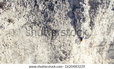 Athletic man climbs very high limestone rock with rope, lead climbing.. Sport climbing outdoor. #1620483229