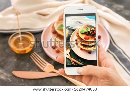 Female food photographer with mobile phone taking picture of pancakes