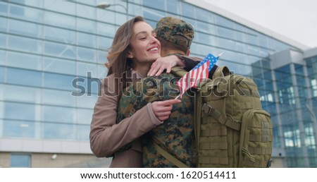 Happy wife meeting his military husband after returning from military service. Young patriotic girl running and cuddling to his boyfriend in military uniform.Concept of military service #1620514411